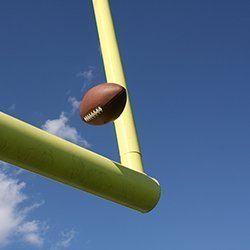 Football being kicked over the goal post